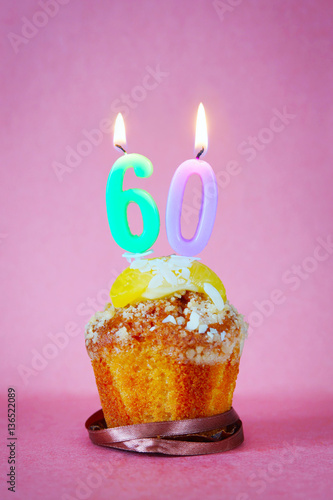 Muffin with burning birthday candles as number sixty on pink background Poster