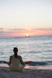 femme en position de yoga au crépuscule sur la plage