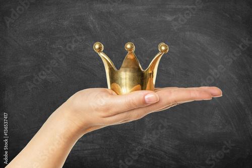 Goldene Krone auf Hand vor Schultafel Poster