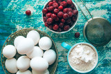 set of cooking cherry pie: a Cup of flour, a sieve, eggs, and frozen cherries in a white bowl on old rustic blue table a top view