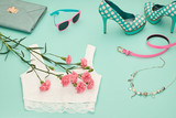 Fototapety Fashion Design Spring girl clothes set,accessories. Trendy sunglasses, lace top, fashion handbag clutch, flowers.Glamor shoes heels.Summer lady.Creative urban.Pastel spring colors.Perspective view