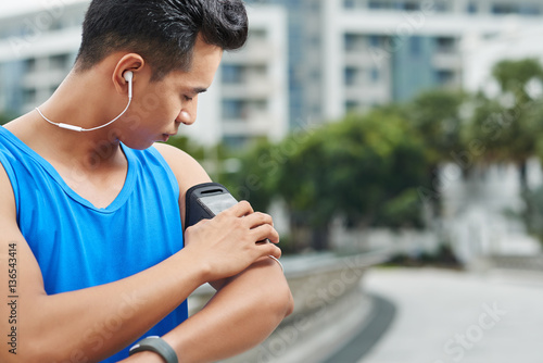 Poster Profile view of young Asian sportsman with stylish haircut putting his smartphon