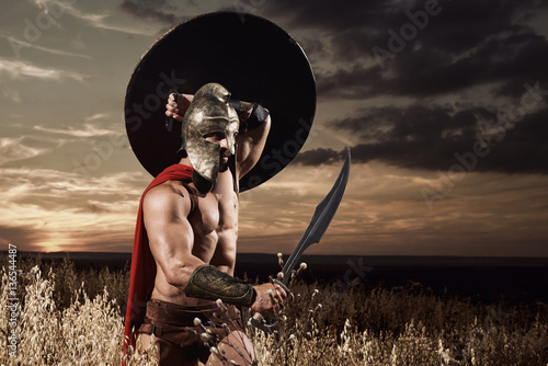 Poster Spartan warrior going forward in attack with sword.