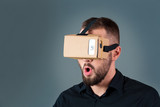 Man using a new virtual reality headset on grey background