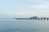 Long concrete jetty with islands and sky background