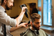 Постер, плакат: Master cuts hair and beard of men in the barbershop
