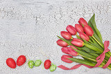 Fresh red tulips and decorative Easter eggs on white table. Top view, copy space