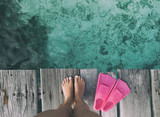 Summer holiday fashion selfie concept - woman feet on a wooden pier at the beach with pink fins