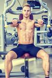 Muscular, shirtless young man in gym exercising pecs on pectoral machine
