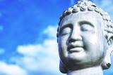 Buddha - ein Kopf vor einem blauen Himmel, als Symbol des Buddhismus.
