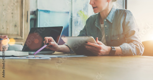 Teamwork. Businesswoman sitting at table and holds tablet computer while showing pen on charts on table. On contrary woman sitting and making notes in notepad. Students learning online, freelance.