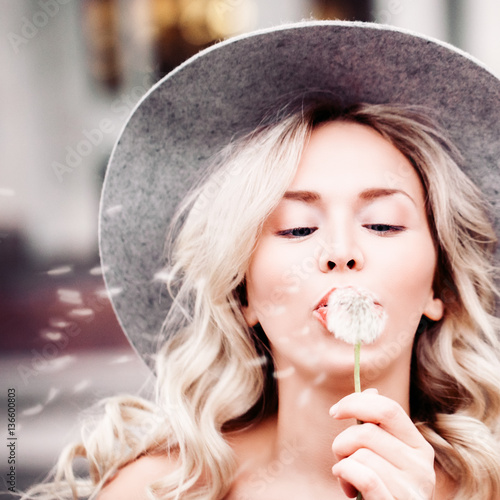 Carefree Woman Blowing a Dandelion Outdoor