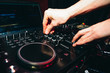 hands of DJ controllers for music on professional mixer for mixing music
