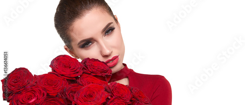 Beautiful model posing with red roses in the studio.