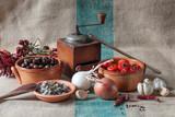 Composizione con attrezzi di legno da cucina, antica macina pepe, olive, capperi e papaccelle napoletane su un sacco di juta