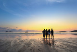 group of happy young people look on beautiful summer sunset at the beach