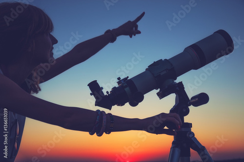 Girl looking at the stars with telescope beside her.