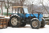 Blue old tractor on a farm in winter