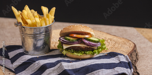Poster Fresh french fries, chips with tasty burger background