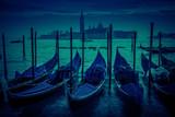 View of gondolas and San Giorgio Maggiore island in the night in Venice, Italy.