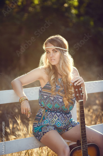 Poster Beautiful hippie girl with guitar in park at sunset