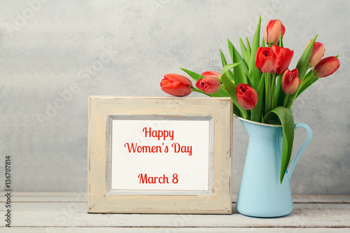 Women day concept, 8th of March with tulip flowers and photo frame on wooden table