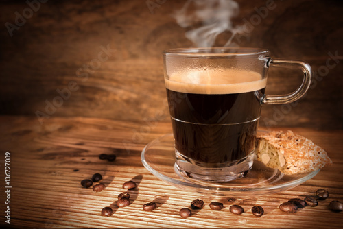 Cup of coffee and beans on dark wooden background
