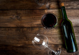 Bottle of wine and two glasses - one empty, one full poured on a wooden table, top view, copy space