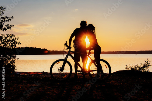 Deurstickers Fietsen couple on a bicycle at sunset by the lake