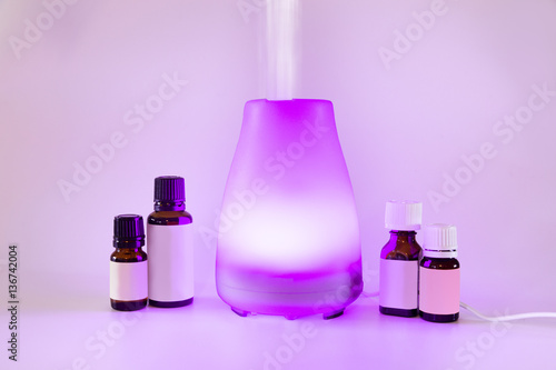 Colorful lit essential oil diffuser with mist and bottles of oils Poster