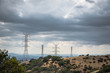 Dark clouds threaten the sky over power lines in the hills overlooking the Los Angeles skyline in the distance.