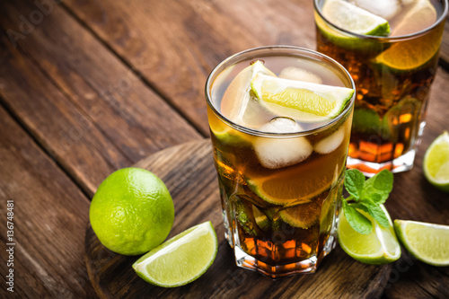 Cuba Libre cocktail with cola, lime and ice in glass, cold longdrink