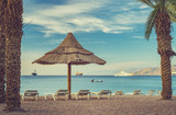 Morning at central beach of Eilat - famous Israeli city located on the Red Sea, its sunny beautiful beaches and resort hotels packed with thousands relaxing and resting tourists from around the world