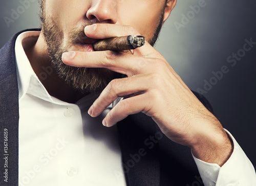 Cigar in hand of men wearing suit and white shirt. Toned skin studio shot over dark background