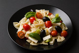 farfalle salad on black plate