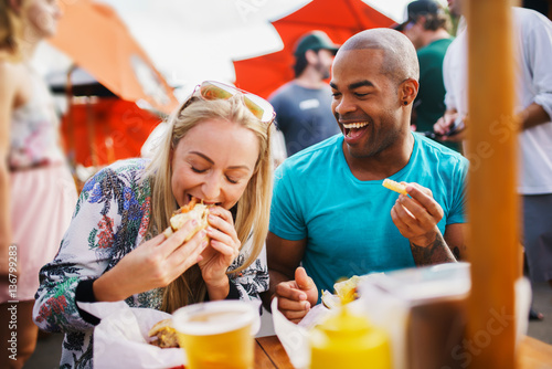 couple having fun time eating burgers and drinking beer