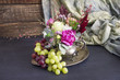 Still life of flowers and grapes on a tray. black background