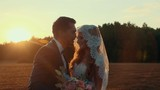 Loving and happiness newlyweds in a field at sunset summer day, embrace and kiss each other on the background of coniferous forest. Tender and romantic feelings of the couple.