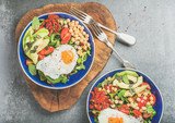 Healthy breakfast bowls with fried egg, chickpea sprouts, seeds, vegetables and greens over grey concrete background, top view. Clean eating, dieting, healthy lifestyle, detox, vegetarian food concept