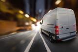 Lieferwagen fährt bei Nacht  durch eine Stadt