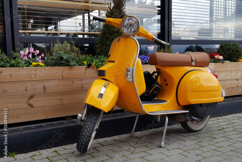 Chalkida, Greece - February 11, 2017: Yellow  scooter parked in a town Chalkida, Greece