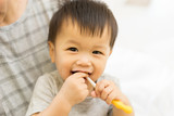Asian baby uses toothbrush - 136858293