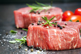 Raw Beef Steaks with spices and Rosemary over Slate