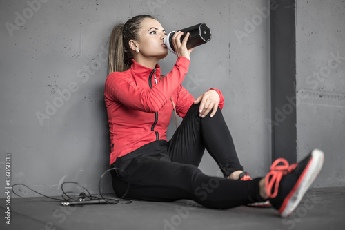 Sportive girl relaxing in gym