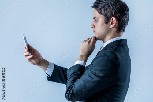 young businessman looking a smart phone Poster