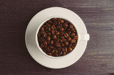 Cup with coffee beans on dark wooden background