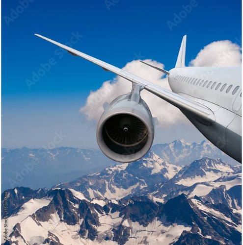 plane flying over the snow-capped mountains. Poster