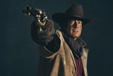 Retro late 1960s western actor. Shooting with revolver. - 136896464