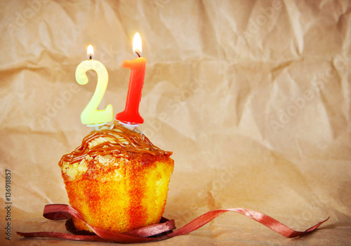 Poster Birthday cake with burning candles as number twenty one on brown paper backgroun