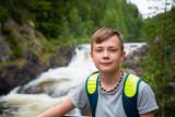 Boy tourist standing near the mountain waterfall
